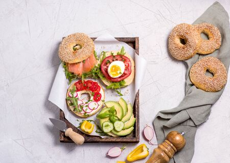 Bagel sandwiches with avocado, salmon, egg and vegetables, healthy snack or brunch, top view