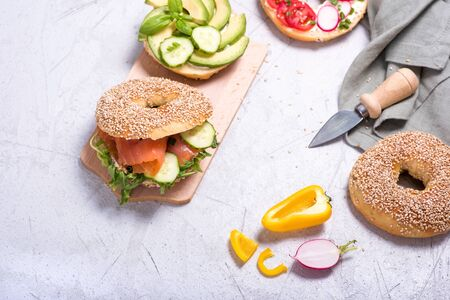 Bagel sandwiches with avocado, salmon, egg and vegetables, healthy snack or brunch, top view, copy space background