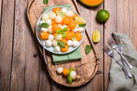 Melon and mozzarella snack, summer salad with cantaloupe melon on wooden background top view, antipasti, italian food