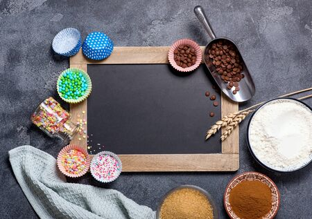Baking ingredients for sweet cake or cupcaked with chalk board copy space background