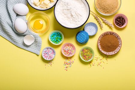 Baking ingredients for cupcakes or muffins on yellow copy space background