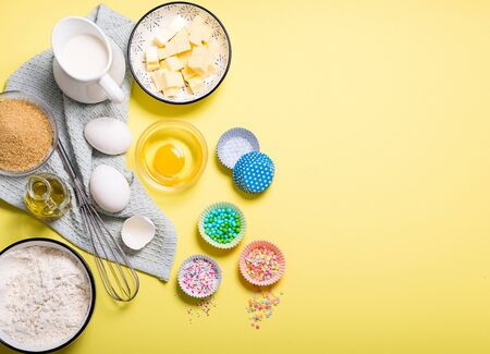 Baking ingredients for cake, cupcakes or muffins on yellow copy space background for text, sugar pearls, eggs, whisk, flour, butter, sugar and milk Banco de Imagens