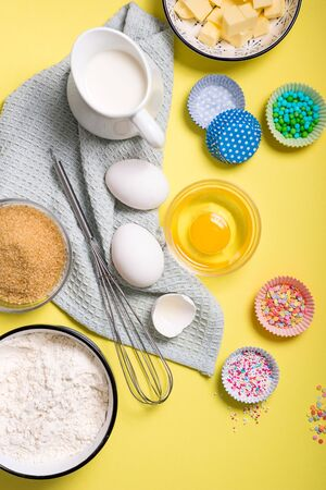 Baking ingredients for cake, cupcakes or muffins on yellow background, sugar pearls, eggs, whisk, flour, butter, sugar and milk