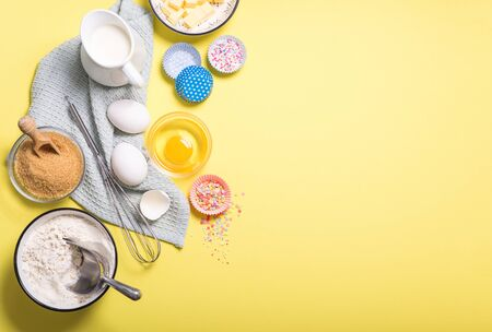 Baking ingredients for cake, cupcakes or muffins on yellow copy space background, eggs, sugar, flour, milk for dough and whisk, place for text Banco de Imagens