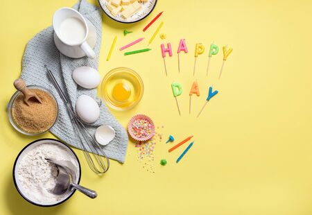 Baking ingredients background for birthday cake on yellow copy space, celebration composition