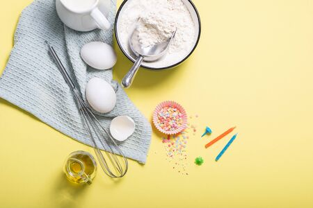 Baking ingredients for birthday cake, cupcakes or muffins on yellow background, sugar pearls, whisk, flour for dough Banco de Imagens