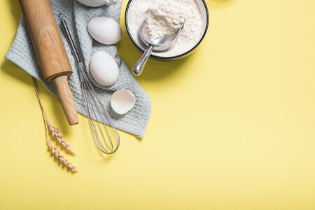 Cooking ingredients, flour, rolling pin and olive oil, top view, place for text yellow background Banco de Imagens