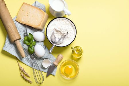Cooking ingredients for pasta, flour, parmesan cheese, basil, eggs, rolling pin and olive oil, top view, italian cooking, yellow background copy space
