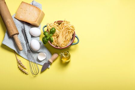 Uncooked pasta, ingredients for cooking, parmesan cheese, eggs, rolling pin and olive oil, italian cooking, yellow background copy space