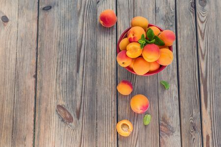 Ripe apricots in a bowl on wooden rustic background copy space, summer fresh organic fruits, vitamins, top view