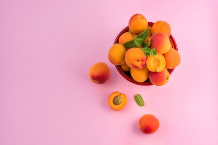 Ripe apricots in a bowl on pink paper background copy space, summer fresh fruits, vitamins, top view