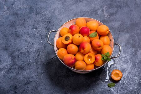 Fresh apricots in colander on dark copy space background, summer fruits, refreshment