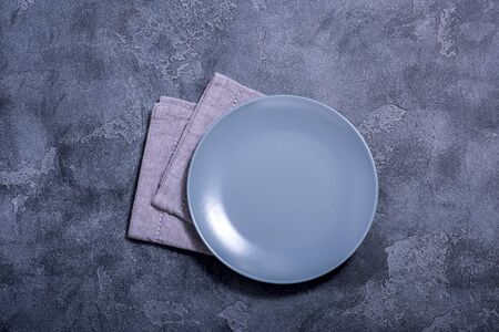 Grey empty plate and napkin on stone background, top view, place for text, copy space Banco de Imagens