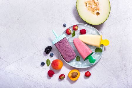 Yellow, purple, pink ice cream with fruits and berries, summer dessert, natural sweets, copy space background