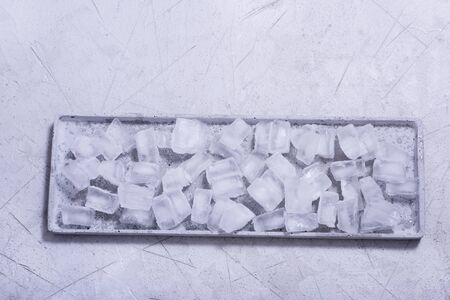 Cubes of ice on concrete background copy space