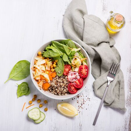 Quinoa salad with chickpeas, spinach, tomatoes, healthy vegan food, diet and clean eating concept on white background, square image
