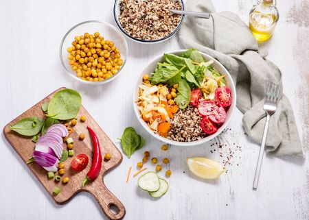 Quinoa salad with chickpeas, spinach, tomatoes, healthy vegan food, diet and clean eating concept, cooking at home, lunch or dinner idea, cozy food Banco de Imagens