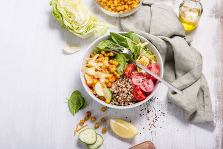Quinoa salad with baked chickpeas, spinach, tomatoes, healthy vegan food, diet and clean eating concept, cooking at home, dinner and lunch ideas, white background