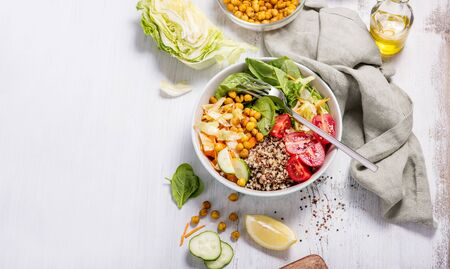 Quinoa salad with baked chickpeas, spinach, tomatoes, healthy vegan food, diet and clean eating concept, cooking at home, dinner and lunch ideas, white copy space background for text