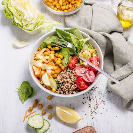 Quinoa salad with baked chickpeas, spinach, tomatoes, healthy vegan food, diet and clean eating concept, cooking at home, dinner and lunch ideas, white background, square image Banco de Imagens