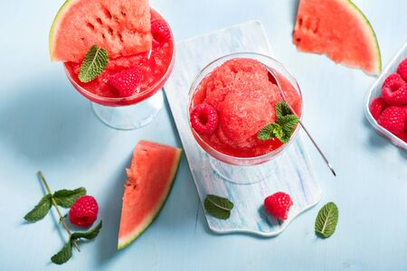 Watermelon sorbet or granita, refreshing summer dessert with strawberries and mint on blue background Stockfoto