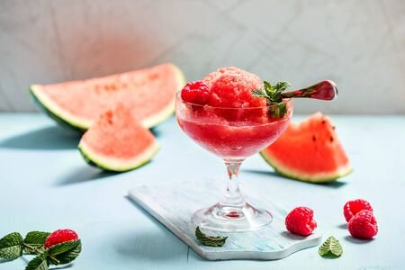 Watermelon sorbet or granita, refreshing summer dessert with strawberries and mint on blue background Banque d'images