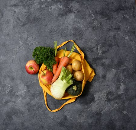 Fresh organic vegetables and fruits in reusable cotton bag, top view, eco-friendly lifestyle and shopping, zero waste, space for text, groceries, vegan food concept Stockfoto