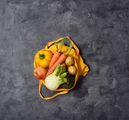 Fresh organic vegetables, fennel bulb, carrots, potatoes in reusable cotton bag, top view, eco-friendly lifestyle and shopping, zero waste, space for text, groceries, vegan food concept