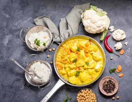 Vegetarian curry with cauliflower and chickpeas served in metal bowls with rice, healthy homemade vegan food, indian cuisine, clean eating concept, Reklamní fotografie