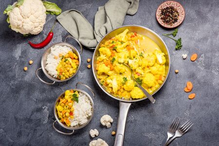 Vegetarian curry with cauliflower and chickpeas served in metal bowls with rice, healthy homemade vegan food, indian cuisine, clean eating concept, Stockfoto