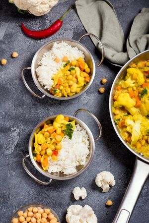 Vegan curry with cauliflower and chickpeas served in metal bowls with rice, healthy homemade vegetarian food, indian cuisine, clean eating concept, cooking at home Banque d'images