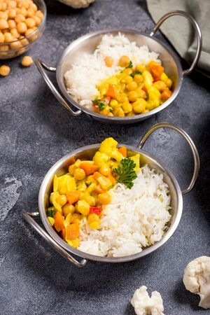 Vegetarian curry with cauliflower and chickpeas served in metal bowls with rice, healthy vegan food, indian cuisine Stockfoto