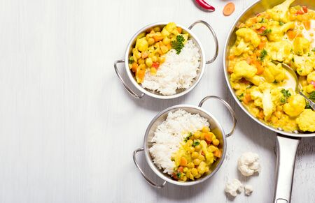 Vegetarian curry with cauliflower and chickpeas served in metal bowls with rice, healthy homemade vegan food, indian cuisine, clean eating concept, copy space background for text