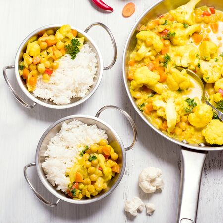 Vegetarian curry with cauliflower and chickpeas served in metal bowls with rice, healthy homemade vegan food, indian cuisine, clean eating concept, square image Banque d'images