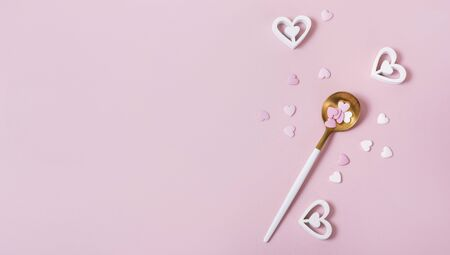 Spoon with hearts, pink romantic background, love symbols, top view, copy space for text, romantic eating concept