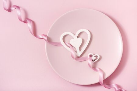 Romantic pink background, plate and hearts with ribbon, Valentine's day celebration, love concept