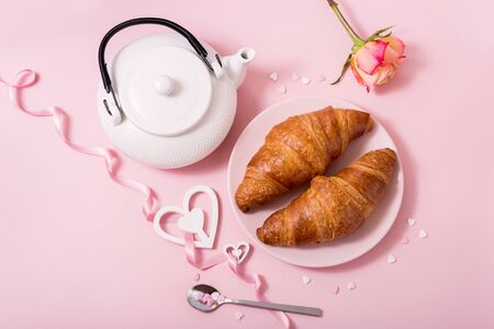 Romantic breakfast with croissants, roses, hearts and tea on pink background, Valentine's day celebration, top view, flat lay Archivio Fotografico