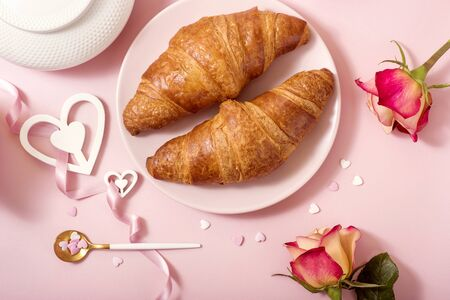 Valentine's day celebration, romantic breakfast with croissants, roses on pink background, top view, love and romance concept