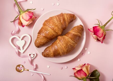 Valentine's day celebration, romantic breakfast with croissants, roses and tea on pink background, love concept, top view