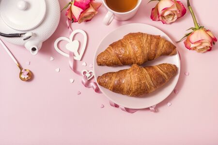 Romantic breakfast with croissants, roses and tea on pink background, Valentine's day celebration, top view
