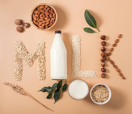 Plant based vegan milk, healthy alternative drink in bottle on wooden background, word milk, letters made of ingredients for plant milk, flat lay on baige background