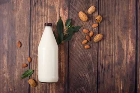 Plant based almond milk, healthy alternative drink in bottle on wooden background, ingredients for plant milk, vegan non dairy milk, flat lay, top view