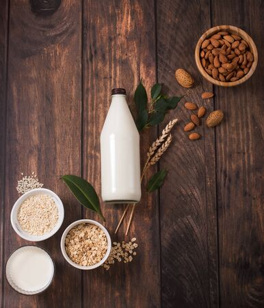 Plant based milk, healthy alternative drink in bottle on wooden background, ingredients for plant milk, almond, oat, rice milk, flat lay