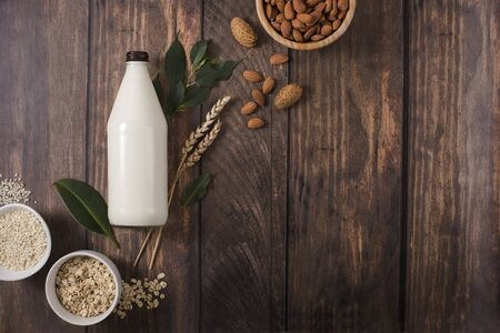Plant based milk alternative in bottle on wooden background, ingredients for plant milk, almond, oat, rice milk, flat lay, copy space for text