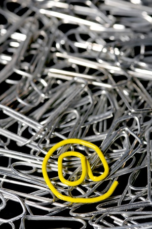 Lots of silver paper clips and one yellow mail paper clip photo