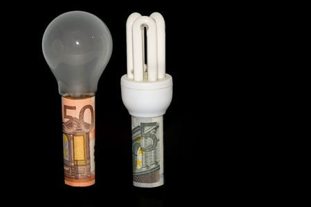 electricity tariff: Two bulbs with banknotes and a black background