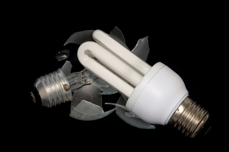 electricity tariff: Energy-saving lamp and old destroyed bulb with a black background