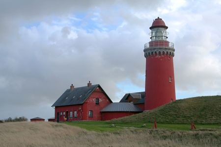 Red lighthouse with a green hill and overcast sky