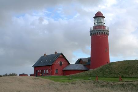 Red Leuchtturm mit einem grünen Hügel und bedecktem Himmel Standard-Bild - 11028562