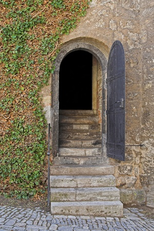 Opened entry door of a dungeon with stairs